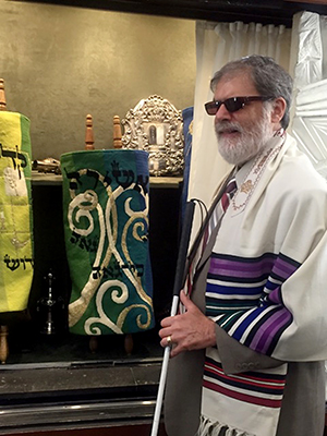 Robert Gumson poses on the bimah of his synagogue.