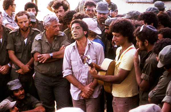 Leonard Cohen, center, performing with Matti Caspi, on guitar, for Ariel Sharon, with arms crossed, and other Israeli troops in the Sinai in 1973. (Courtesy of Maariv).
